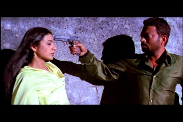Maqbool mockingly holds a gun to Nimmi's head